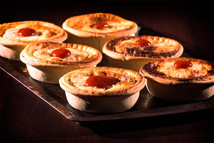 Freshly baked meat pies with sauce