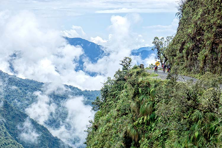 """Mountain bikers riding the famous downhill trail """"Road of death"""" in Bolivia"""