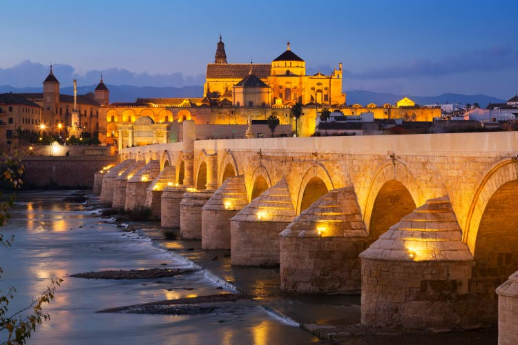 Roman bridge over Guadalquivir river in evening. Cordoba, Spain