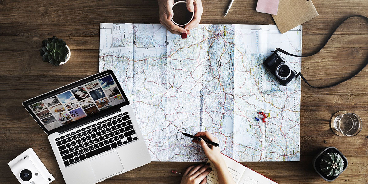 Map with laptop and people planning travels