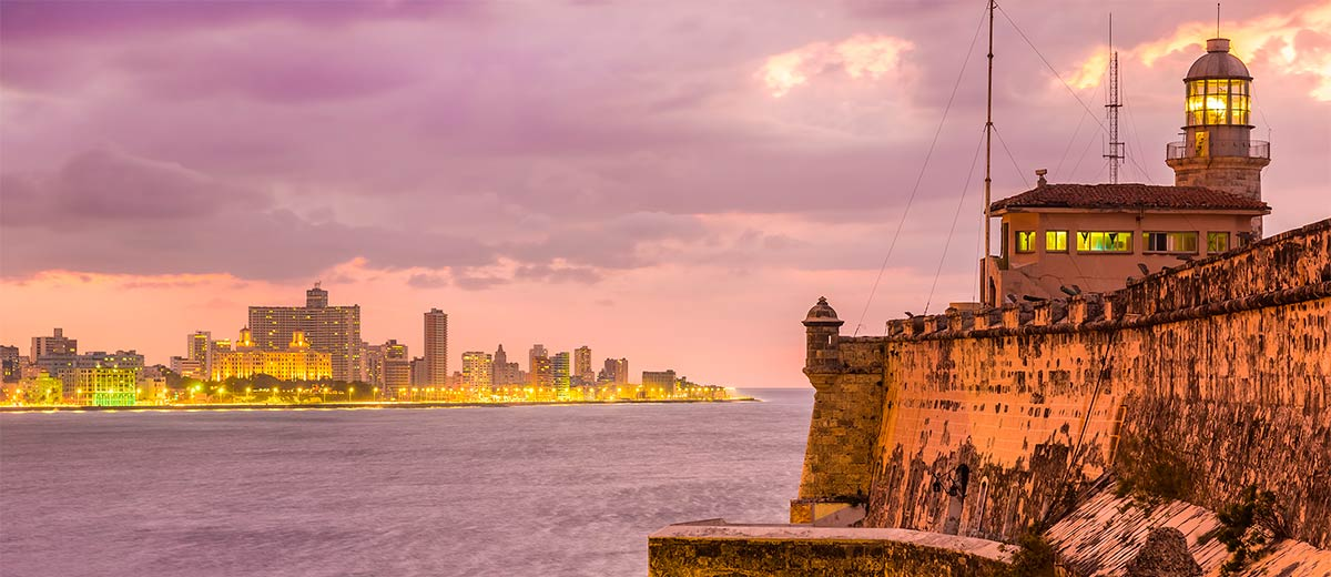 Beautiful sunset in Havana with El Morro lighthouse illuminated Featured Image