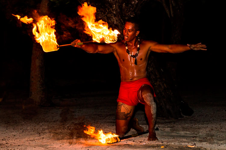 Polynesian man performs traditional fire dance in Tahaa