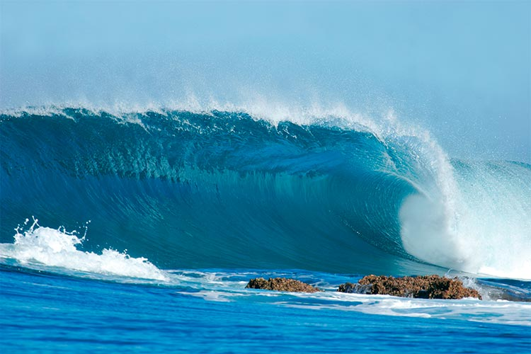 A beautiful blue wave crashes into the rocks at Inhaca Island